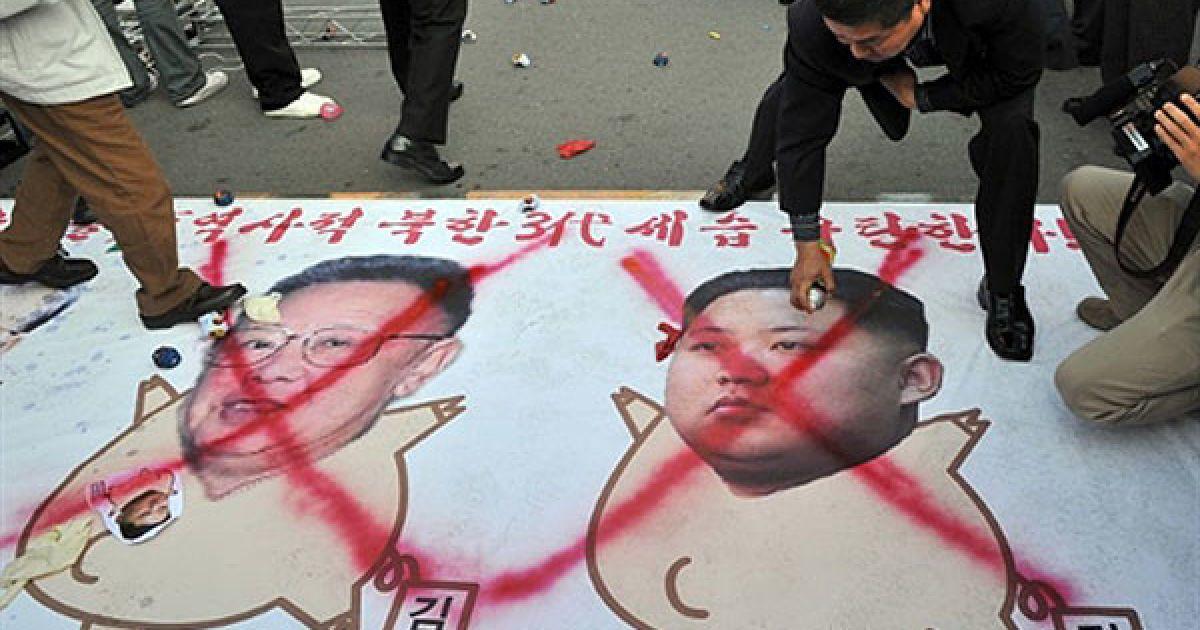 """Республіка Корея, Сеул. Південнокорейські активісти малюють червоні хрести на карикатурах лідера Північної Кореї Кім Чен Іра та його молодшого сина Кім Чен Ина під час мітингу, на якому було засуджено """"комуністичну династію"""", що вже три покоління керує Північною Кореєю. Північна Корея офіційно назвала Кім Чен Ина наступним лідером, який займе місце свого хворого батька. @ AFP"""