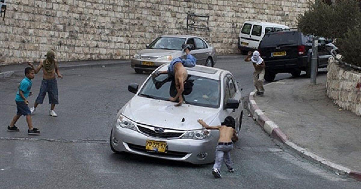 Ізраїльський водій збиває палестинського юнака, який стояв посеред групи молодих людей, що почали кидати каміння у ізраїльські автомобілі в арабському районі Єрусалиму Сільван @ AFP
