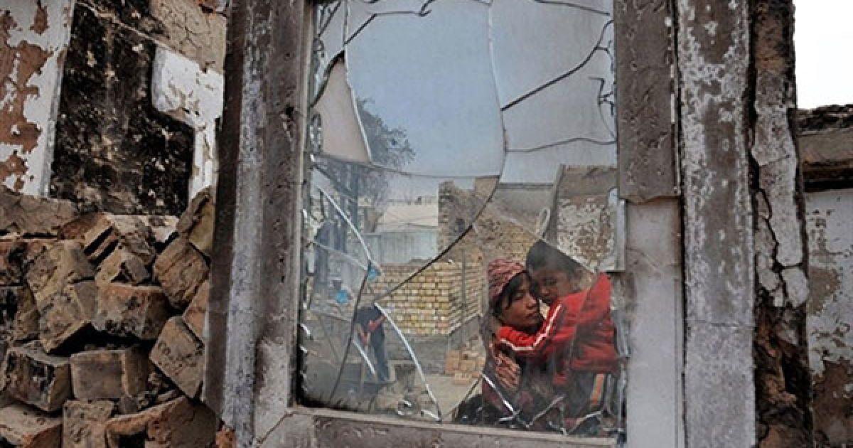 Киргизстан, Ош. Узбецька жінка та її син дивляться на свій зруйнований будинок у селі Шарк неподалік від міста Ош. Сили безпеки у Киргизстані перебувають у стані підвищеної готовності, аби уникнути спалаху насильства напередодні парламентських виборів в країні. Президент Киргизстану Роза Отунбаєва заявила, що країна намагається оправитися від етнічного кровопролиття. @ AFP
