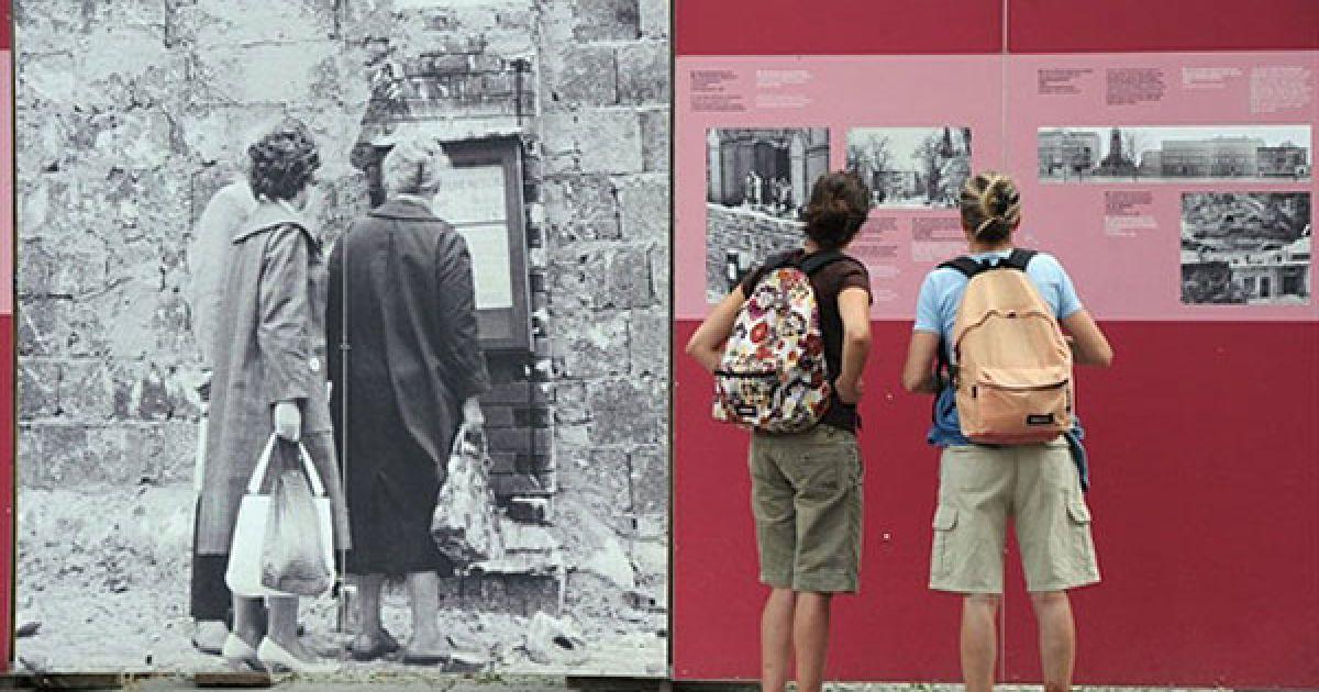 Німеччина, Берлін. Дівчата роздивляються фотографії на Берлінській стіні біля меморіалу на Бернауер-штрассе у Берліні. Мешканці Берліну відзначили 49-ту річницю зведення Берлінської стіни. @ AFP