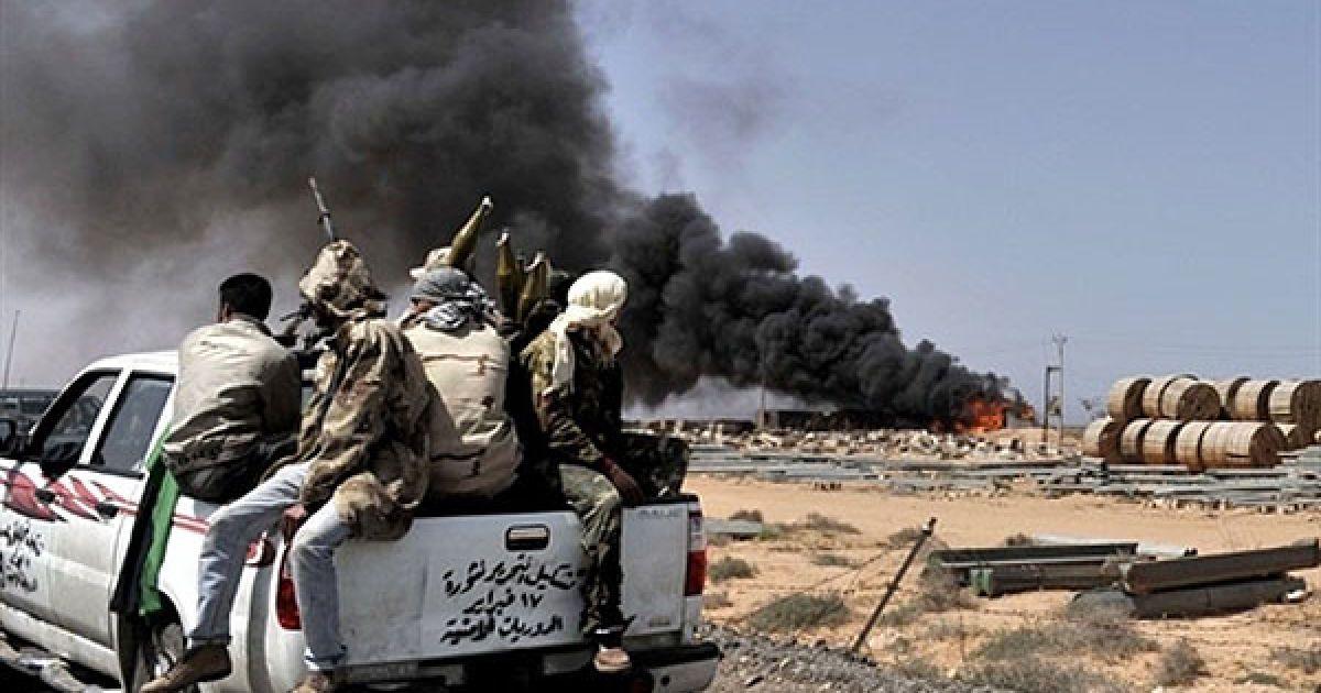Лівійська Арабська Джамахірія, Бен Джавад. Дим від вибухів видно, доки лівійські повстанці просуваються на захід до рідного міста Муаммара Каддафі Сірте. НАТО погодилося взяти на себе повне командування військовою операцією в Лівії. @ AFP
