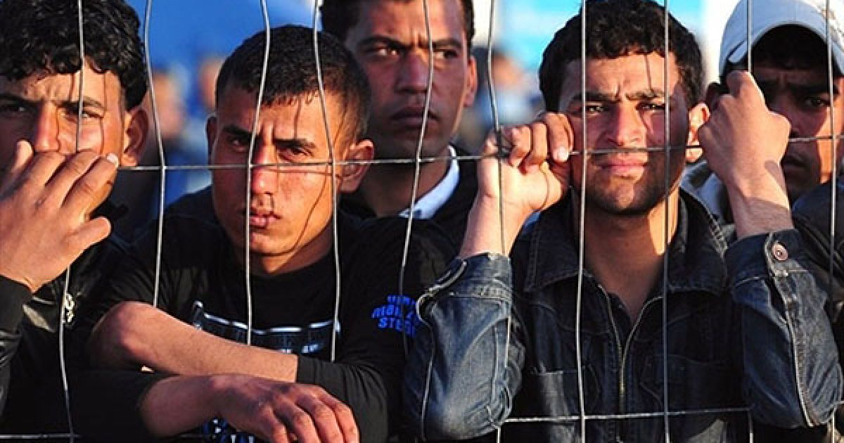 Італія, Лампедуза. Туніські мігранти чекають на прибуття човна на острові Лампедуза. Сотні тунісців були переміщені до наметових таборів на півдні Італії. @ AFP