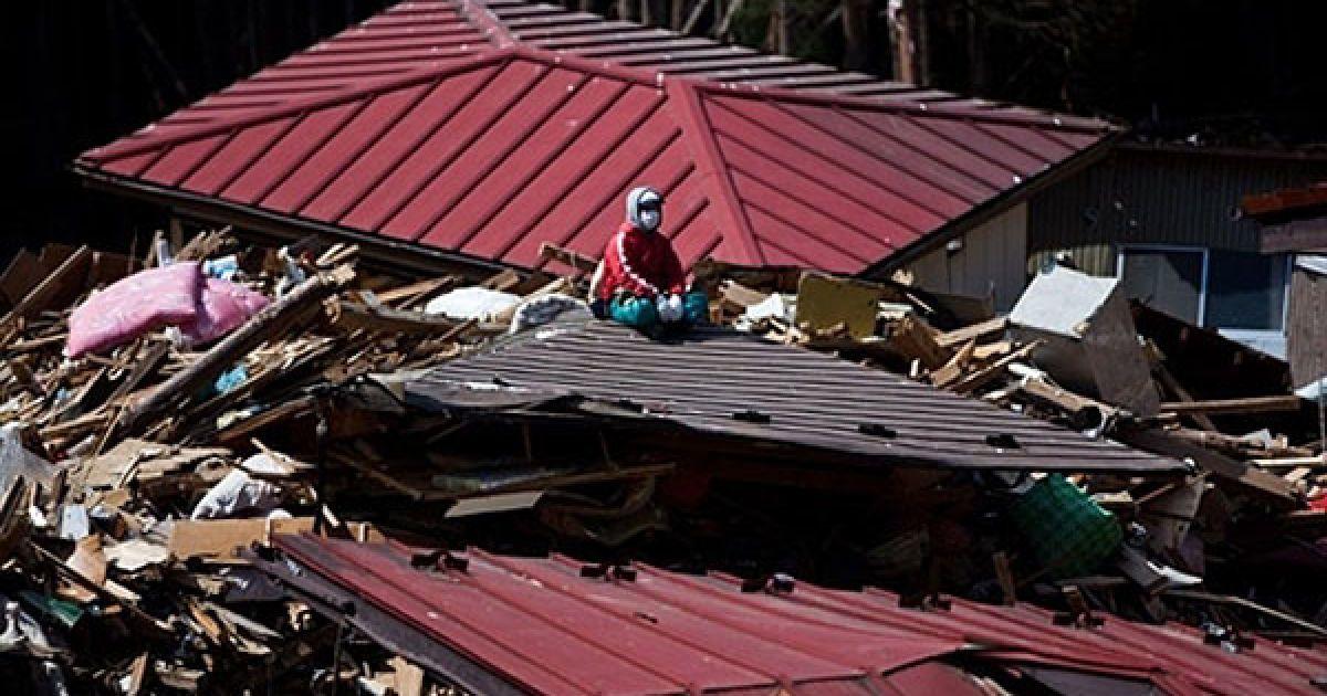 Японія, Мінамісанріку. Рибак Ютака Ватанабе сидить на даху свого зруйнованого будинку, доки він шукає зниклих членів своєї родини. Число загиблих і зниклих безвісті після руйнівного землетрусу та цунамі в Японії перевищило 28 тисяч осіб. @ AFP