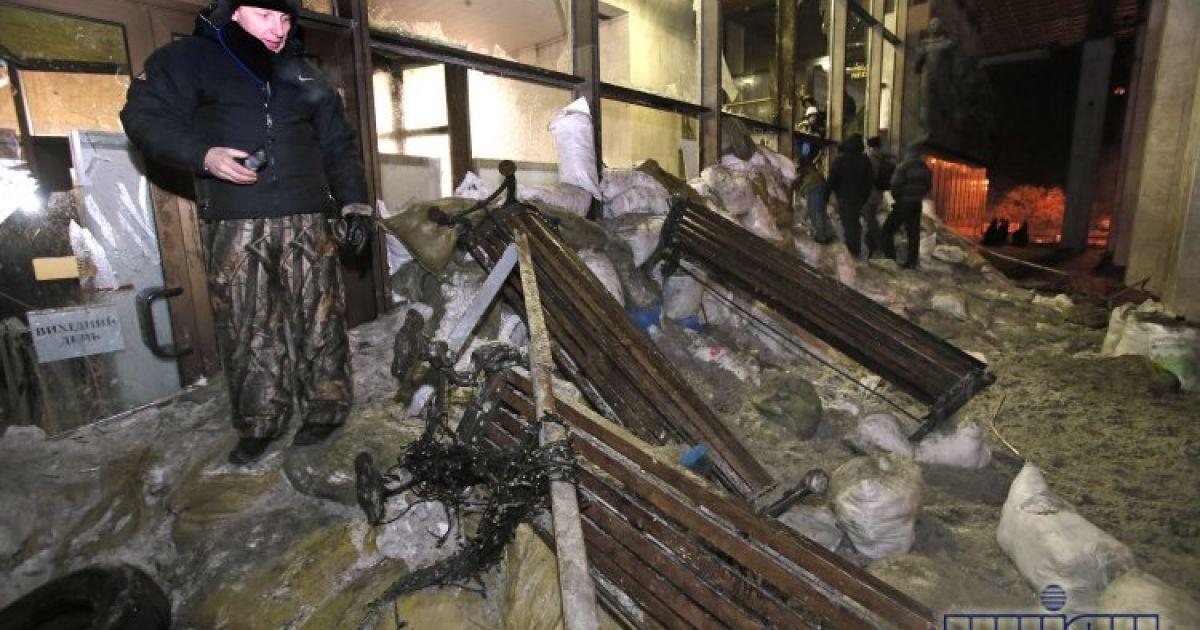 После ночного штурма здания люди выносят мусор @ УНІАН