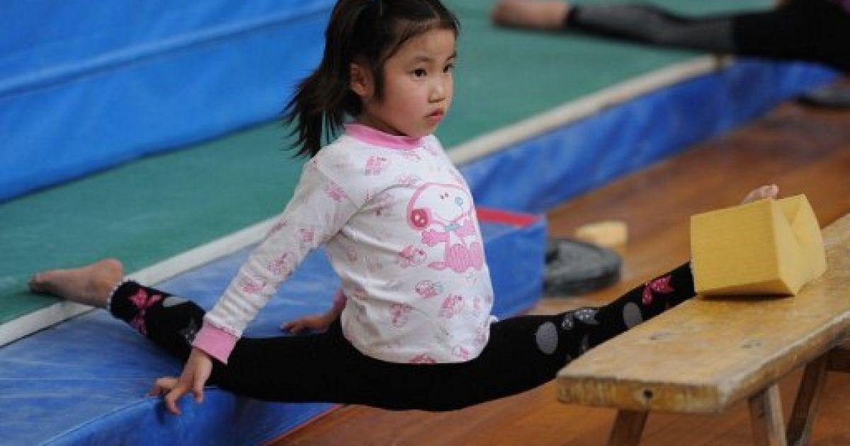 Китай, Хефей. Юну гімнастку готують у спеціальній спортивної школи в місті Хефей. Потенційні чемпіонки мають виснажливий графік тренувань. @ AFP