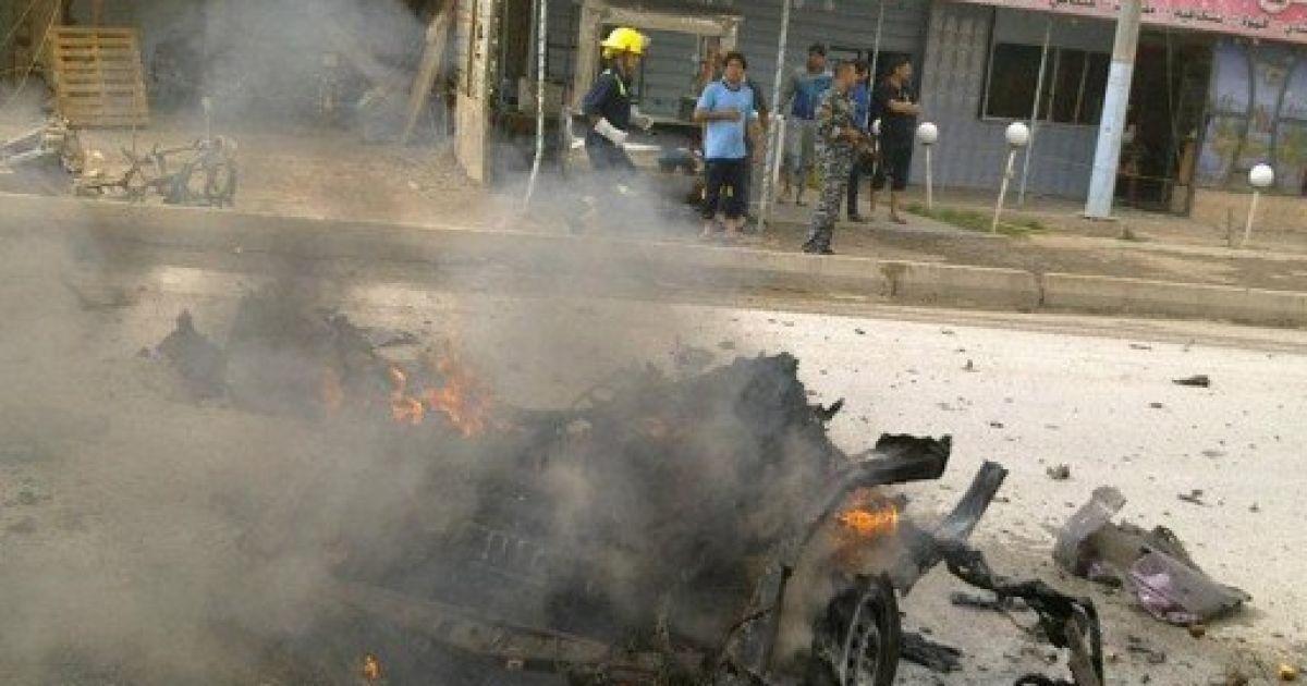 Ірак, Рамаді. Люди дивляться, як догорає автомобіль, який вибухнув в іракському місті Рамаді в західній провінції Анбар. @ AFP