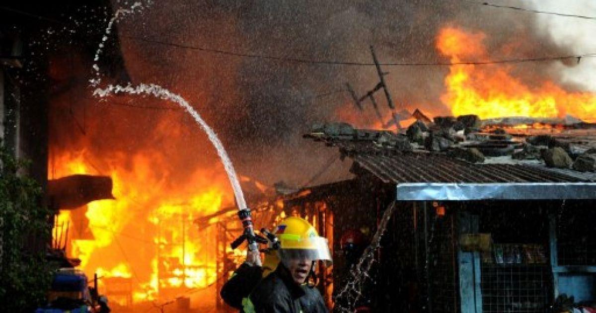 Філіппіни, Маніла. Пожежні намагаються загасити вогонь, який охопив район нелегальних поселенців у Манілі. В результаті пожежі близько 150 сімей залишились без будинків. @ AFP