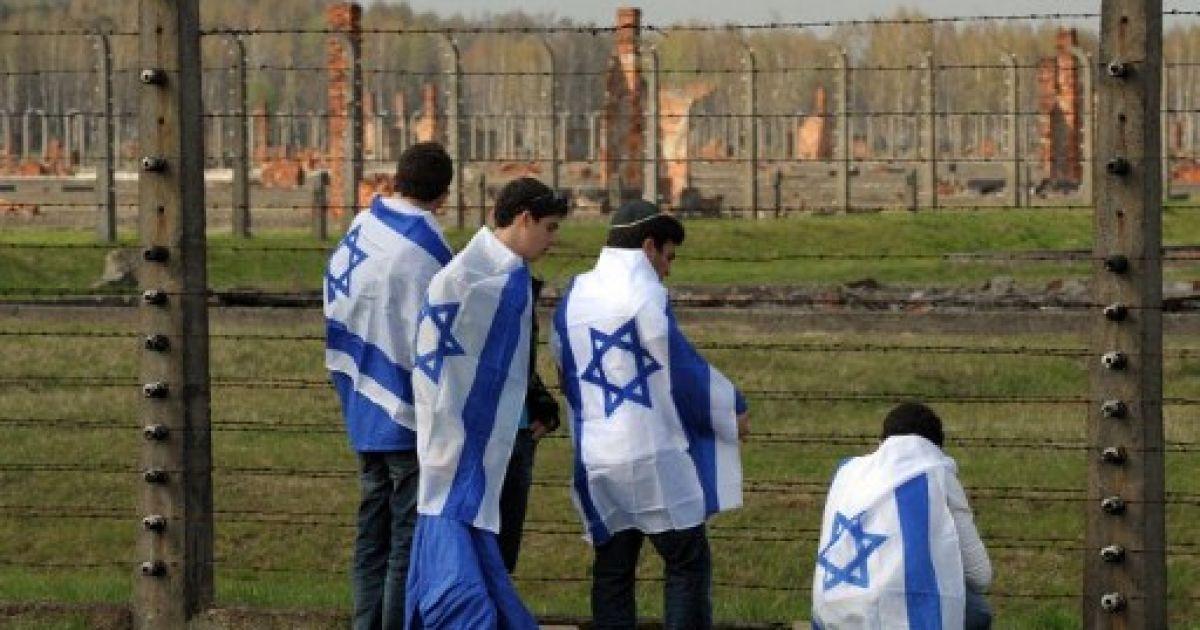 """Польща, Освенцім. Юнаки, загорнуті у ізраїльські прапори, беруть участь у Марші живих, який стартував у таборі смерті """"Освенцім-Біркенау"""" в Польщі. Щорічний Марш живих проводять на згадку про 6 млн євреїв, убитих під час Голокосту. @ AFP"""