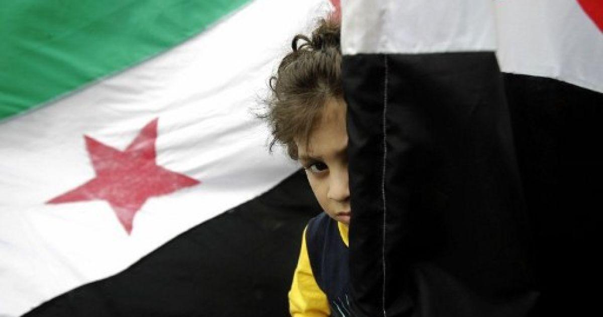 """Ліван, Бейрут. Дитина ховається за сирійськими прапорами під час демонстрації прихильників руху """"Джамаа Ісламія"""" проти режиму президента Башара аль-Асада. @ AFP"""
