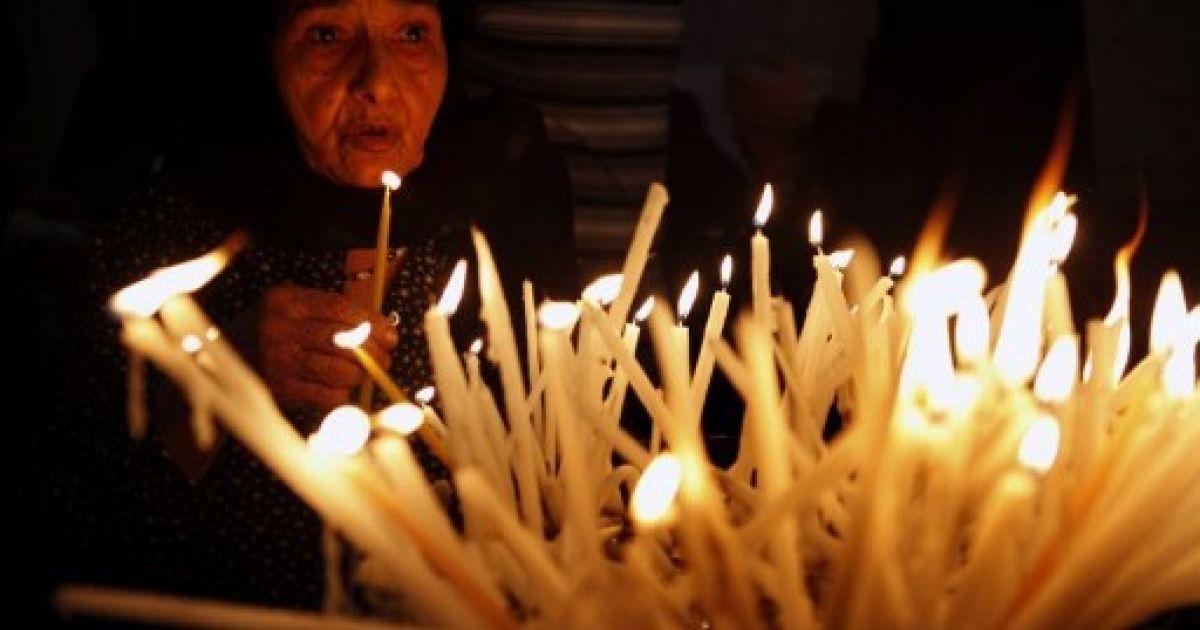 Єрусалим. Коптська православна запалює свічки у храмі Гроба Господня Єрусалимі. @ AFP