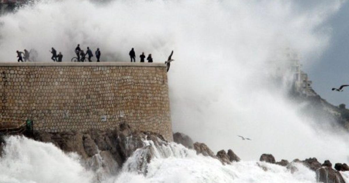 Франція, Ніцца. Люди дивляться на високі хвилі, які накривають набережну Ніцци. Південь Франції потерпає від сильних дощів і повені, сотні людей були евакуйовані, троє загинули, тисячі будинків залишилися без електрики. @ AFP