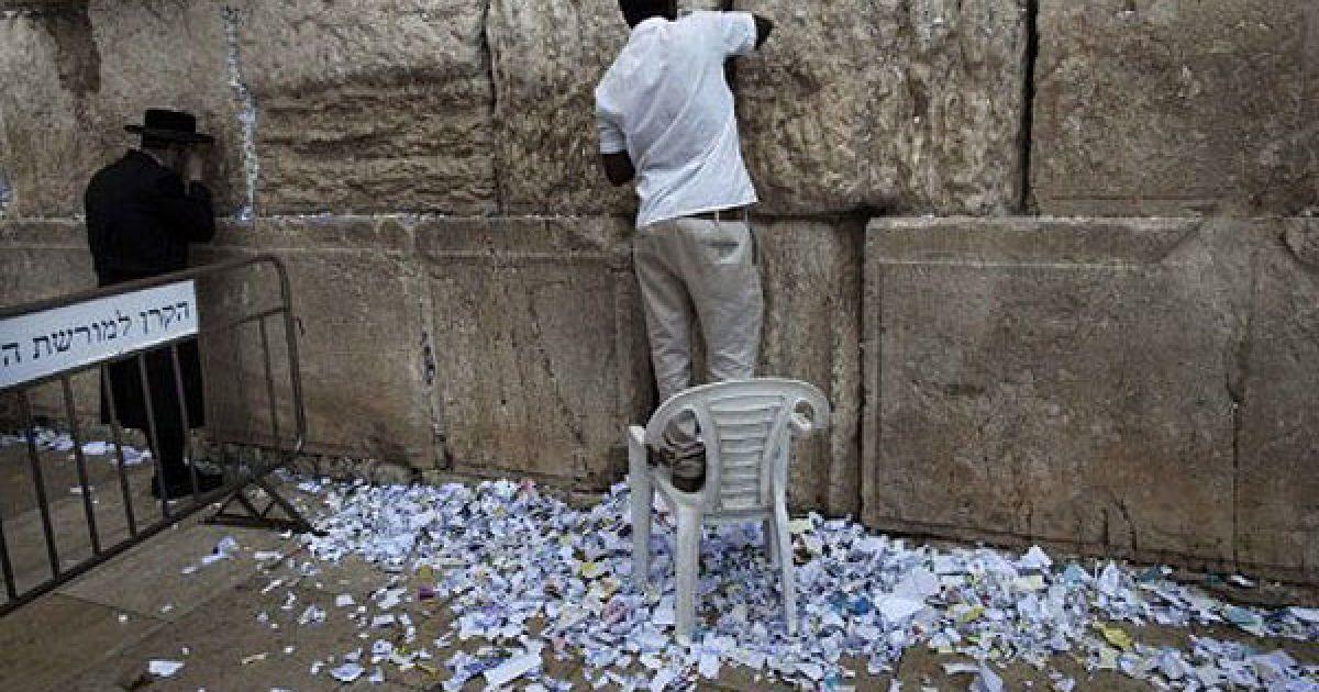 Єрусалим. Співробітник прибирає паперові записки і молитви, залишені в Стіні Плачу, під час підготовки до святкування єврейського Нового року. @ AFP