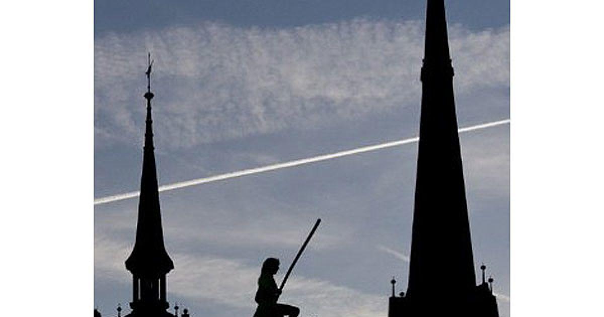 Німеччина, Галле. Жінка-канатоходець на велосипеді пересувається по мотузці над ринковою площею перед церквою у місті Галле, Східна Німеччина. @ AFP