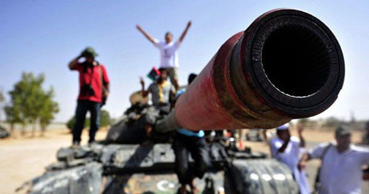 Лівійська Арабська Джамахірія, Сірт. Бійці Перехідної національної ради входять на танку на околицю міста Сірт, доки літаки НАТО бомбардують позиції військ Муаммара Каддафі. @ AFP