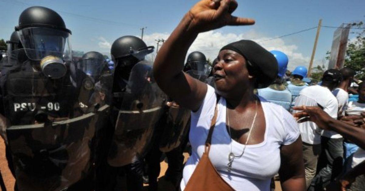 Ліберія, Монровія. Прихильниця опозиційної партії Конгрес демократичних змін (CDC) співає пісні перед кордоном ліберійської поліції та сил ООН з підтримки миру. Акція протесту в Монровії переросла у криваві зіткнення, одна людина була убита. @ AFP