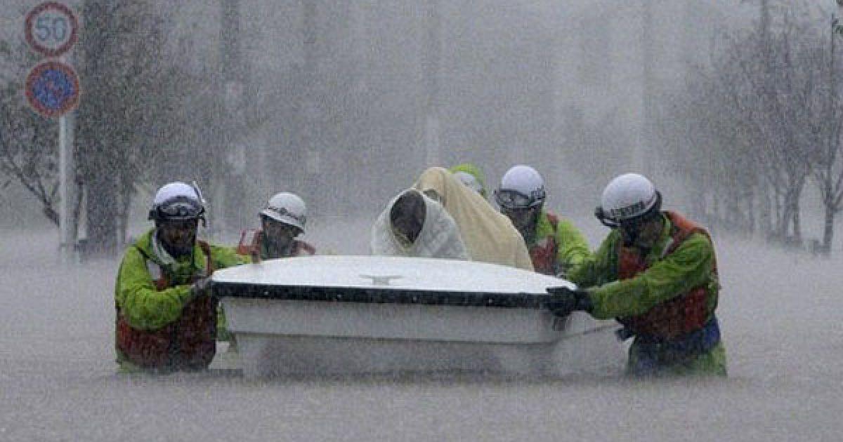 Японія, Нагоя. Рятувальники перевозять евакуйованих у човні через затоплене місто Нагоя у префектурі Аїті. Сотні тисяч людей в Японії були змушені залишити свої домівки через наближення потужного тайфуну, який приніс із собою проливні дощі і загрозу зсувів і паводків. @ AFP