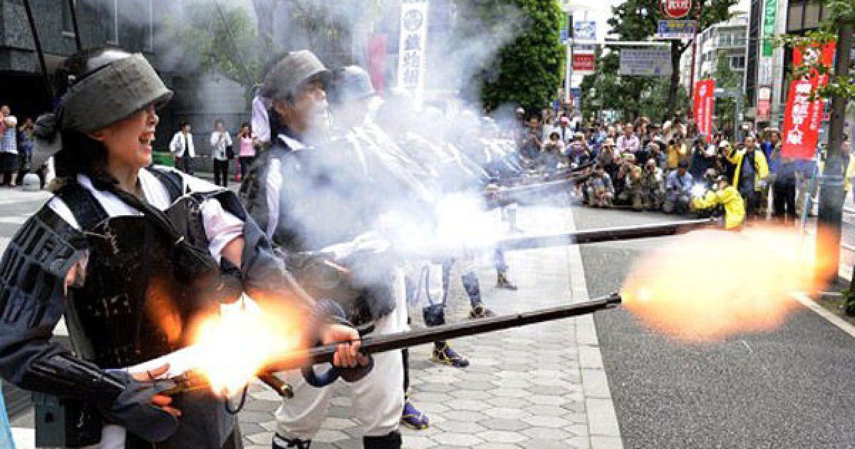 Японія, Токіо. Люди у формі воїнів-самураїв епохи династії Едо демонструють старовинну гнотову вогнепальну зброю, яку привезли до Японії з Європи в середині 16-го століття. @ AFP