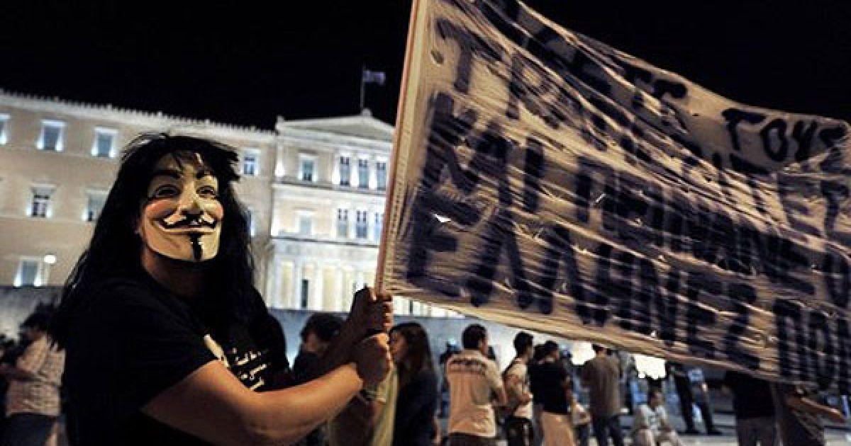 Греція, Афіни. Демонстрант у масці бере участь в акції протесту перед парламентом Греції проти нових заходів жорсткої економії. @ AFP