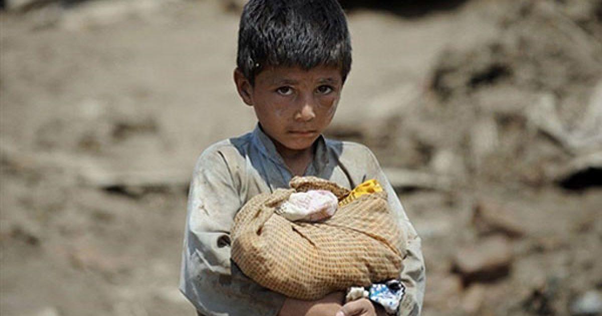 Пакистан. Афганський хлопчик несе свій нехитрий скарб, коли він разом з іншими постраждалими від повені людьми має вилітіти з табору Азакель поблизу міста Ноушера. ООН терміново відрядила до Пакистану свого високого посланника для вирішення нагальних проблем місцевого населення. Більше 1500 осіб загинуло, і майже 3,2 млн. людей постраждали від руйнівних повеней, які перетворились у гуманітарну катастрофу. У країні виникають побоювання, що складна ситуація може призвести до продовольчої кризи, оскільки велика частина сільськогосподарських угідь була зруйнована потоками води. @ AFP
