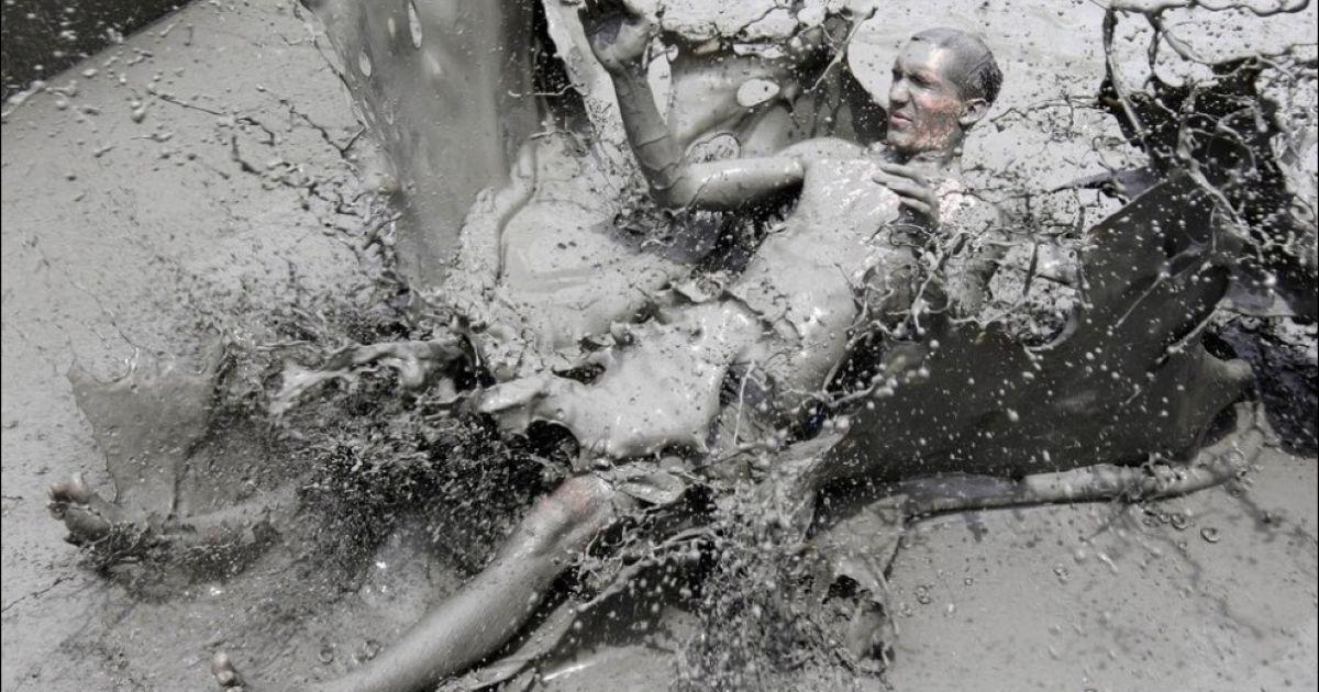 Люди із задоволенням валяються у багнюці @ Getty Images