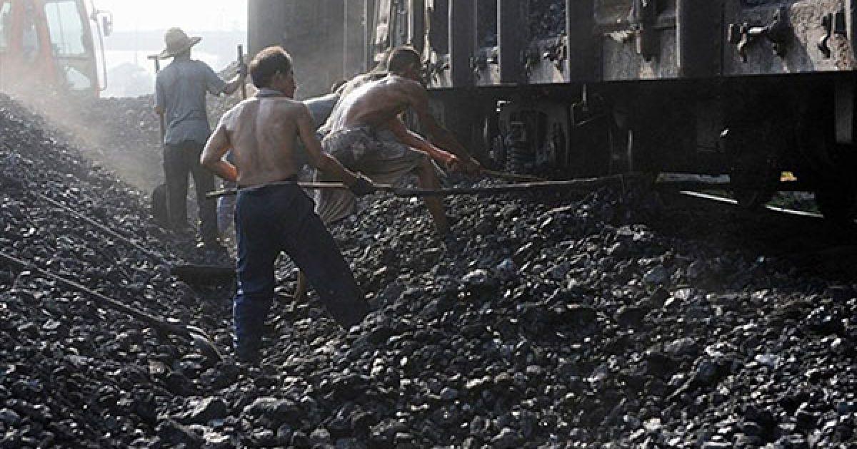 Китай, Хефей. Китайські шахтарі вивантажують вугілля з потягу у Хефеї, провінція Аньхой. Китай за рахунок вугілля задовольняє близько 70 відсотків своїх потреб у електроенергії. @ AFP