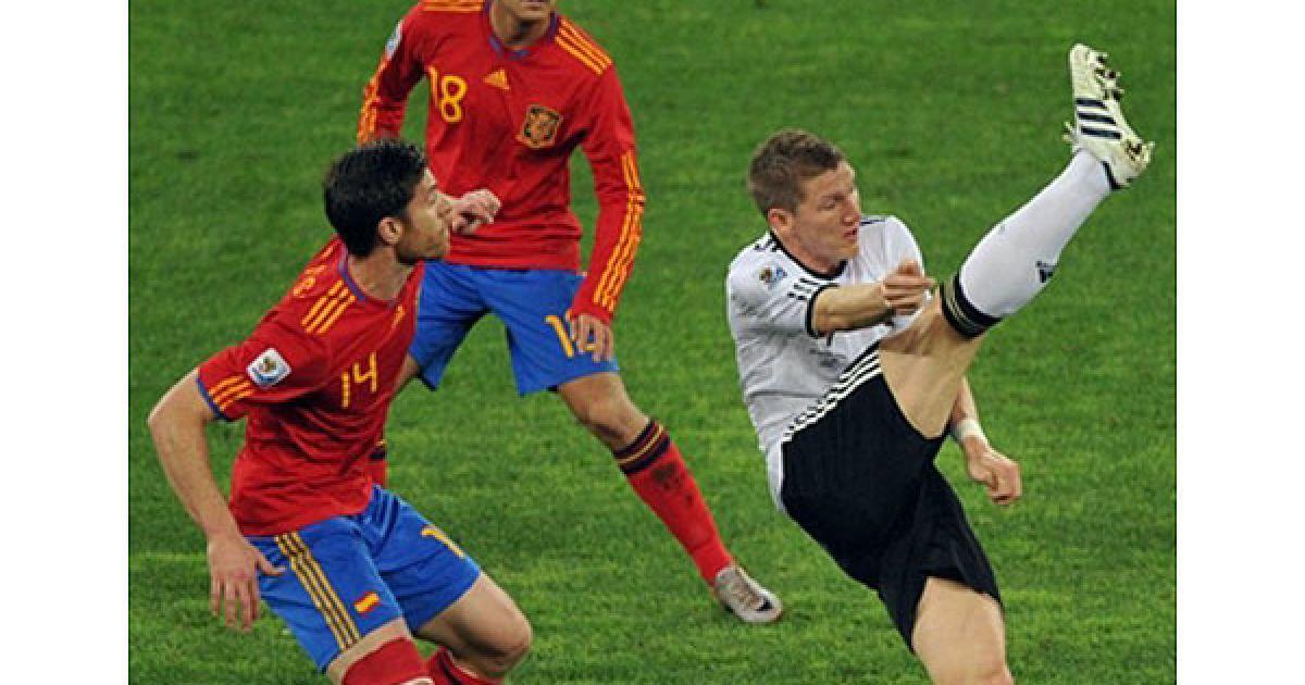 Хабі Алонсо і Педро дивляться, як Швайнштайгер демонструє свою розтяжку. @ AFP