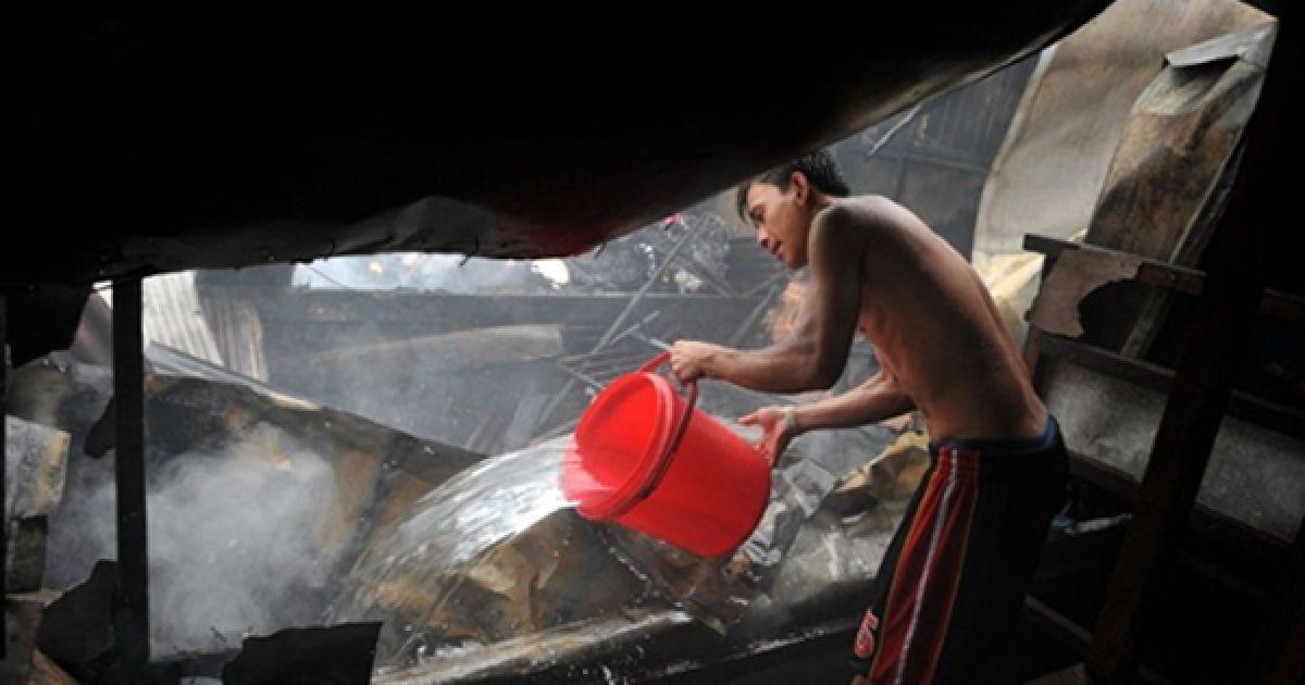 Чоловік намагається загасити пожежу у нетрях Маніли. Філіппінським пожежникам вдалося врятувати 150 родин, які жили у покинутих будинках. @ AFP