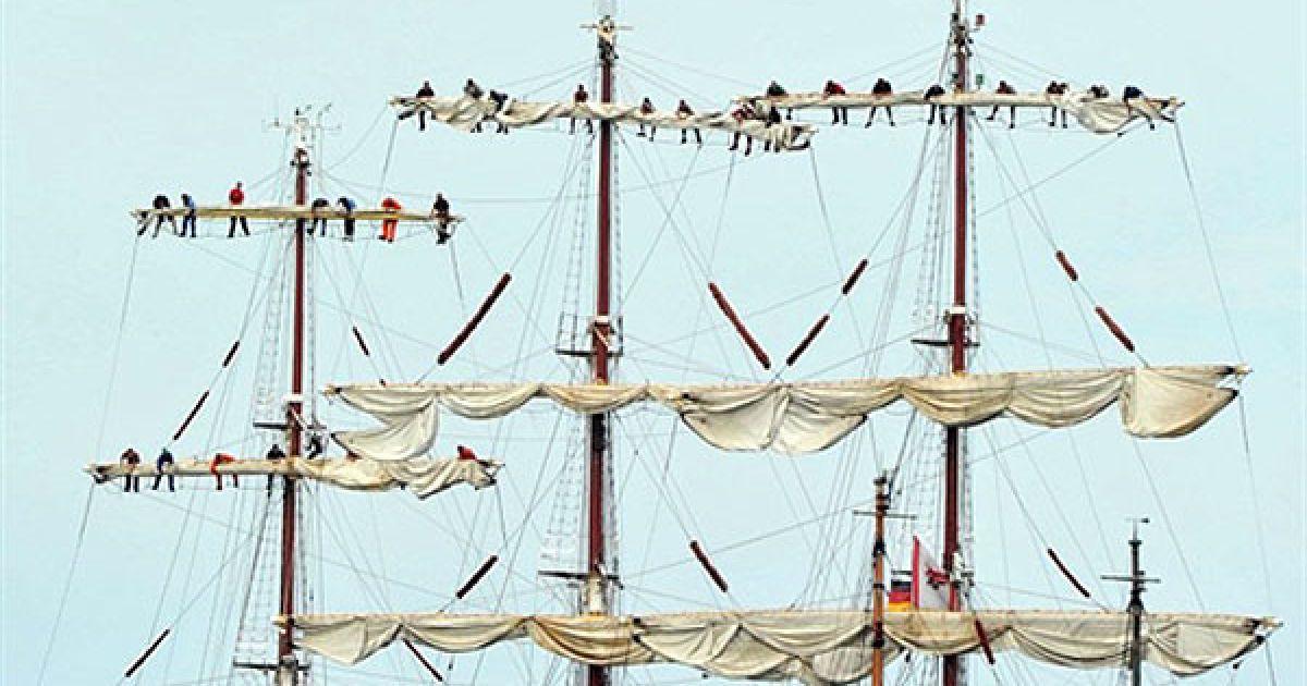 Німеччина. Чоловіки прибирають вітрила на парусному човні, який прокладає собі шлях через Балтійське море під час вітрильної регати Hanse Sail у Варнемюнде, на північному сході Німеччини. Організатори очікують, що регату відвідають до 1 млн глядачів. @ AFP