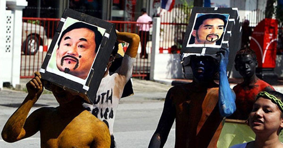 Таїланд, Наратхіват. Тайські студенти тримають над головами маски із фотографіями конкуруючих політиків: колишнього прем'єр-міністра у вигнанні Такісна Чинавати і прем'єр-міністра Абхісіта Веджадживи, під час участі у параді напередодні дня народження королеви Сірікіт, у південній провінції Таїланду. День народження королеви Сірікіт відзначатиметься по всій країні 12 серпня. @ AFP