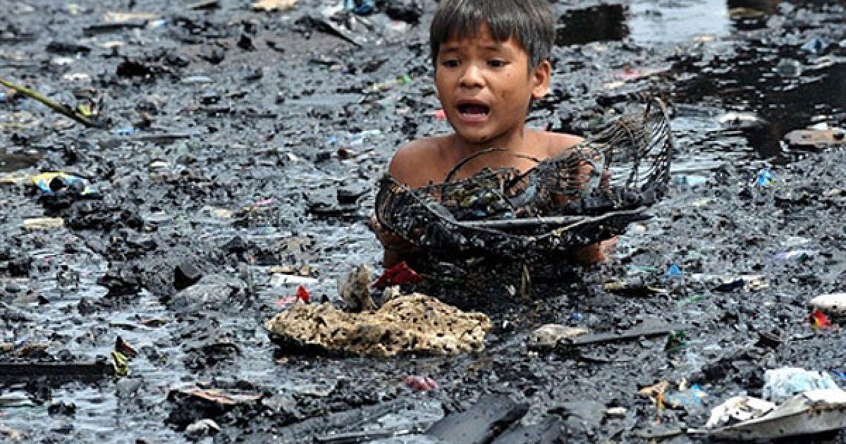 Філіппіни, Маніла. Дитина шукає речі у воді і намагається врятувати обвуглені предмети після гасіння пожежі у нетрях Малабон у Манілі. В результаті пожежі пожежні не змогли врятувати від вогню більше 300 будинків. Влада почала розслідування пожежі, в якій ніхто не постраждав. @ AFP