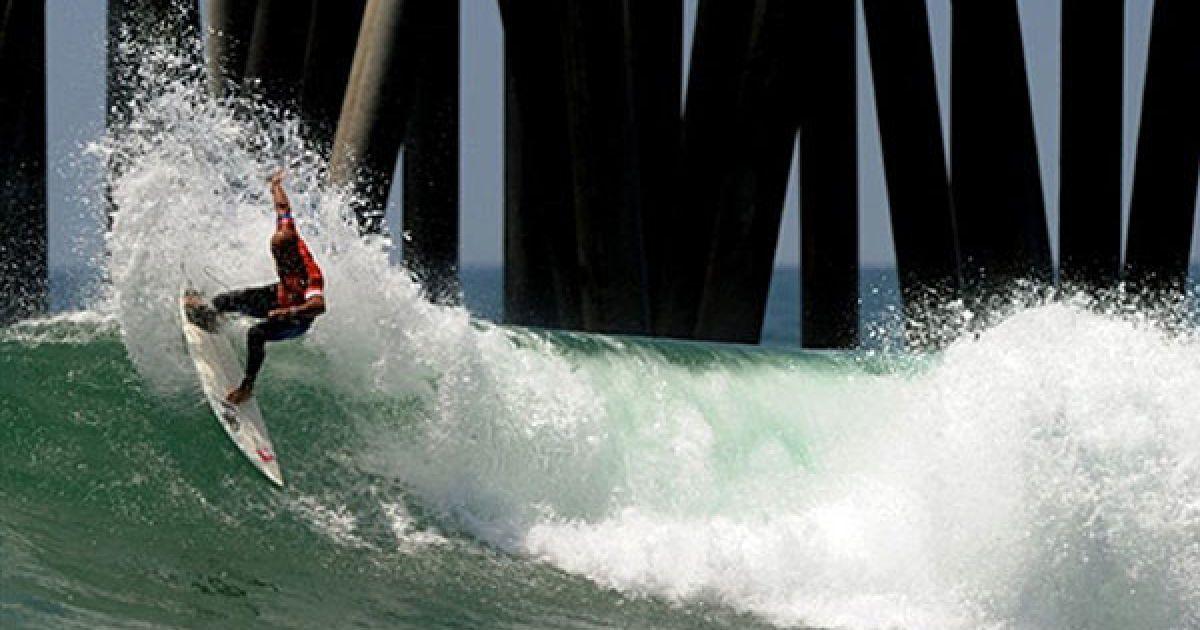 США, Хантінгтон-Біч. Чемпіон світу з серфінгу американець Келлі Слейтер під час виконання вправи біля пірса на Відкритому чемпіонаті США з серфінгу. Чемпіонат з серфінгу цього року проходить у п'ятдесят перший раз, а пірс Хантінгтон вважається історичною батьківщиною серфінгу у Каліфорнії. @ AFP