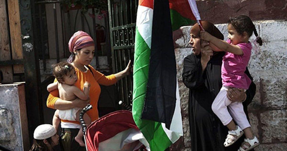 Єрусалим. Палестинська жінка (праворуч), чий будинок був окупований ізраїльськими поселенцями, несе на руках свою дитину, яка тримає палестинський прапор. Поруч із ними проходить ізраїльська жінка-поселенець, яка тепер мешкає у цьому спірному будинку у східному районі Єрусалиму Шейх-Джаррах. В Єрусалимі провели акцію протесту з нагоди першої річниці масового виселення палестинських родин з їхніх будинків. @ AFP