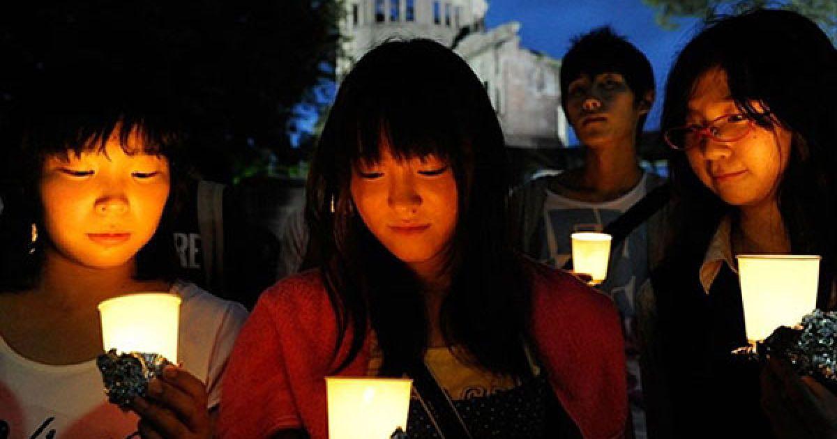 Японія, Хіросіма. Японські підлітки тримають свічки під час молитви на згадку про жертв атомного бомбардування міст Хіросіма і Нагасакі у 1945 році. Акцію пам'яті провели у меморіальному парку міста Хіросіма, де цього року відзначать 65-ту річницю першого атомного нападу у світі. @ AFP