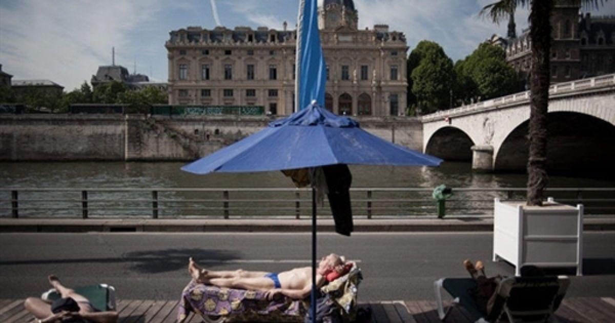 """Люди відпочивають на """"Паризькому пляжі"""". Вже дев'яте літо поспіль набережна Сени перетворюється на повноцінний пляж із піском та пальмами. Закриється """"Паризький пляж"""" 20 серпня. @ AFP"""