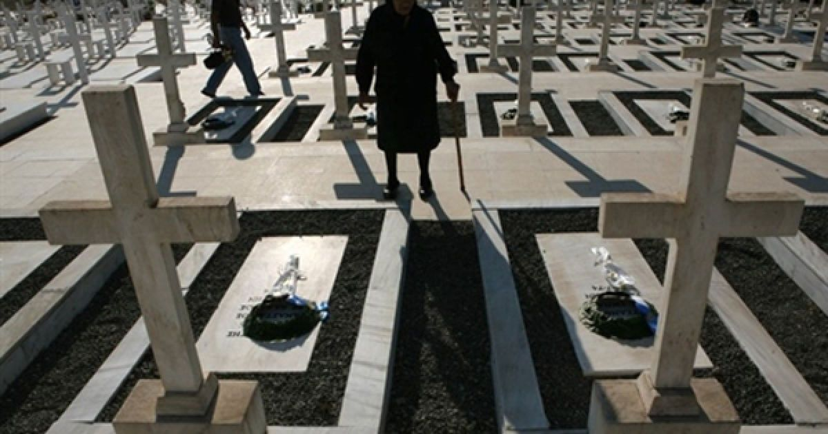 Жінка покладає квіти до могили грецьких солдатів, які загинули під час турецького вторгнення на Кіпр 1974 року на кладовищі у Нікосії у день 36-ої річниці конфлікту. @ AFP