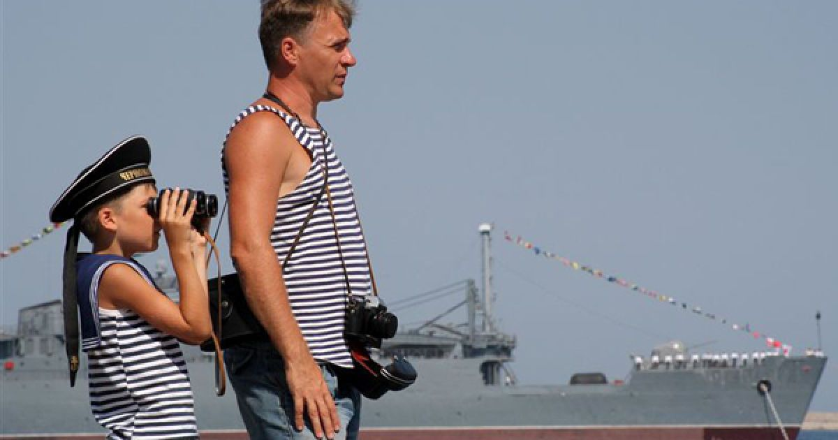 Чоловік із сином спостерігають за репетицією параду до Дня ВМФ РФ. @ PHL.com.ua