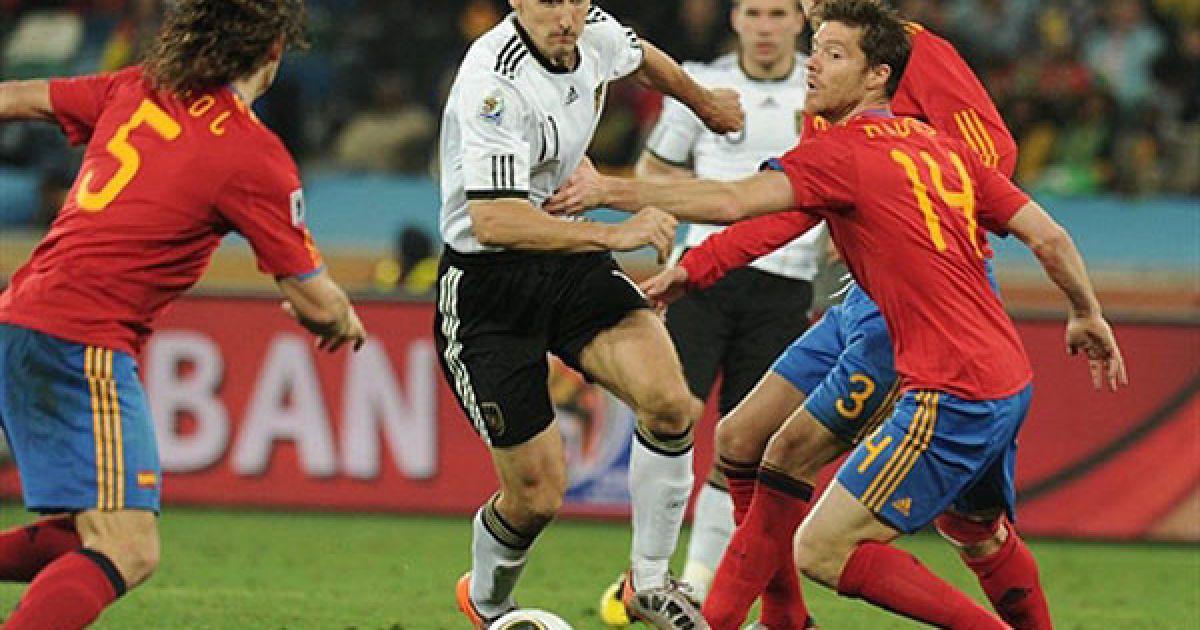 Мірослав Клозе намагається прорватись з м'ячем повз Хабі Алонсо, Джерарда Піке і Карлоса Пуйоля @ AFP