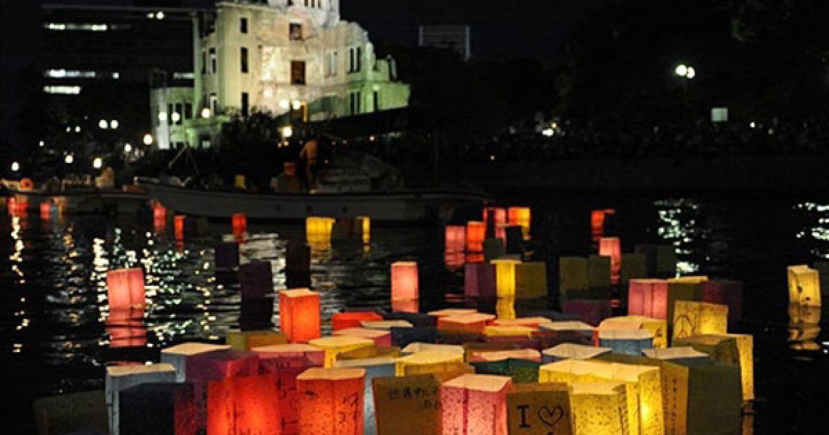 Японія, Хіросіма. Паперові ліхтарі зі свічками пливуть річкою Мотоясу поруч із будівлею Куполу атомної бомби у місті Хіросіма. Цього року виповнюється 65 років з моменту атомних бомбардувань японських міст Хіросіма і Нагасакі. У пам'ятних заходах в Японії взяли участь представники понад 70 країн, у тому числі вперше до церемонії приєднався представник Сполучених Штатів. @ AFP
