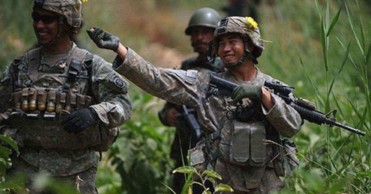 Афганістан, Аргандаб. Американські солдати сміються і чіпляють один одному на шоломи жовті квіти під час спільного патрулювання американських військових і національних сил безпеки Афганістану у долині Аргандаб, провінція Кандагар. У світі зростає невдоволення діями американців під час війни у Афганістані. Президент США Барак Обама став на захист американських військових, заявивши що певний прогрес був досягнутий у питанні забезпечення безпеки у країні. @ AFP