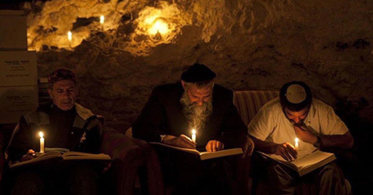 Ізраїль, Бейт-Меїр. Кабаліст Рабі Урі Ревах і його учні читають релігійні тексти при свічках під час нічних уроків Каббали у гірській печері поблизу Єрусалиму. Десять євреїв-ортодоксів раз на тиждень збираються у печері, щоб протягом ночі вивчати Каббалу, читати тексти з єврейських священних книг. @ AFP
