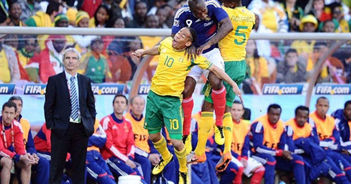 Південна Африка, Блумфонтейн. Півзахисник збірної ПАР Стівен Пієнаар, нападаючий збірної Франції Джібріль Сіссе і захисник збірної Південної Африки Анеле Нгконгка ведуть запеклу боротьбу за м'яч, доки тренер збірної Франції Раймон Доменек спостерігає за ними. У ПАР відбувся матч між збірними Франції та Південної Африки. @ AFP