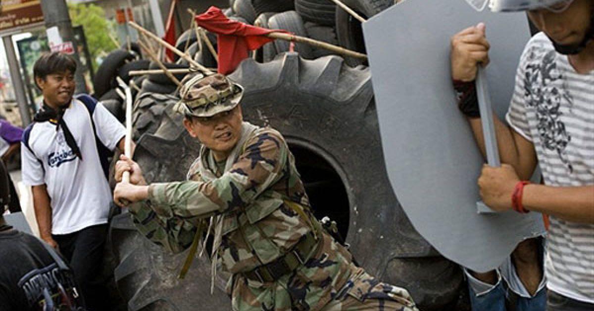 """Таїланд, Бангкок. Генерал-майор опозиційного руху """"Червоних сорочок"""" випробовує на міцність саморобний щит. Опозиціонери здійснюють регулярне патрулювання вулиць за межами укріпленого табору опозиції у фінансовому центрі Бангкока. @ AFP"""