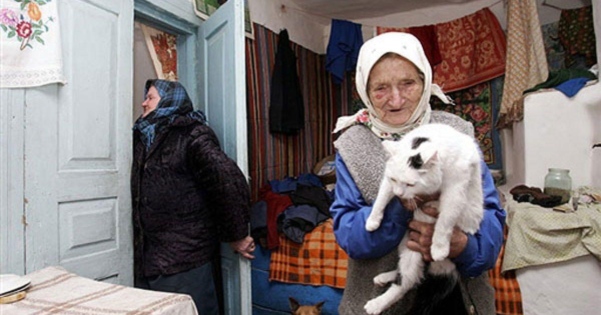 Україна, село Ільїнці, 30-км зона, 2006 рік. Зіна Гузенко, 93 роки, тримає свого кота. @ AFP