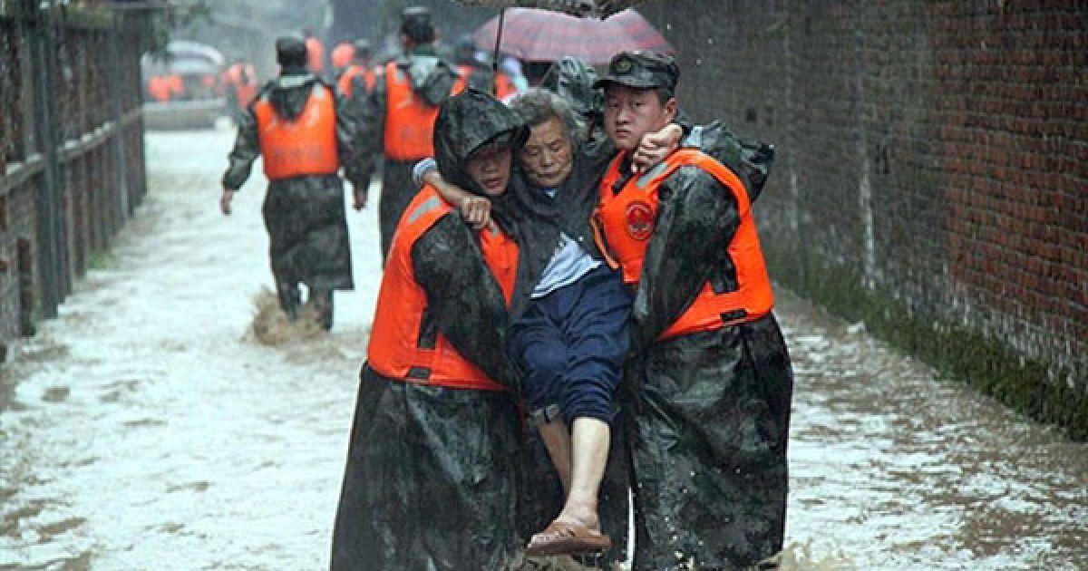 Китай. Китайські рятувальники допомагають евакуювати літню жінку. Південно-східна провінція Китаю Фуцзянь потерпає від повенів. Голова КНР Ху Цзіньтао закликав активізувати зусилля з ліквідації наслідків численних повеней на півдні країни, викликаних проливними дощами. Жертвами повеней вже стали щонайменше 175 осіб, кілька сотень зникли безвісти. @ AFP
