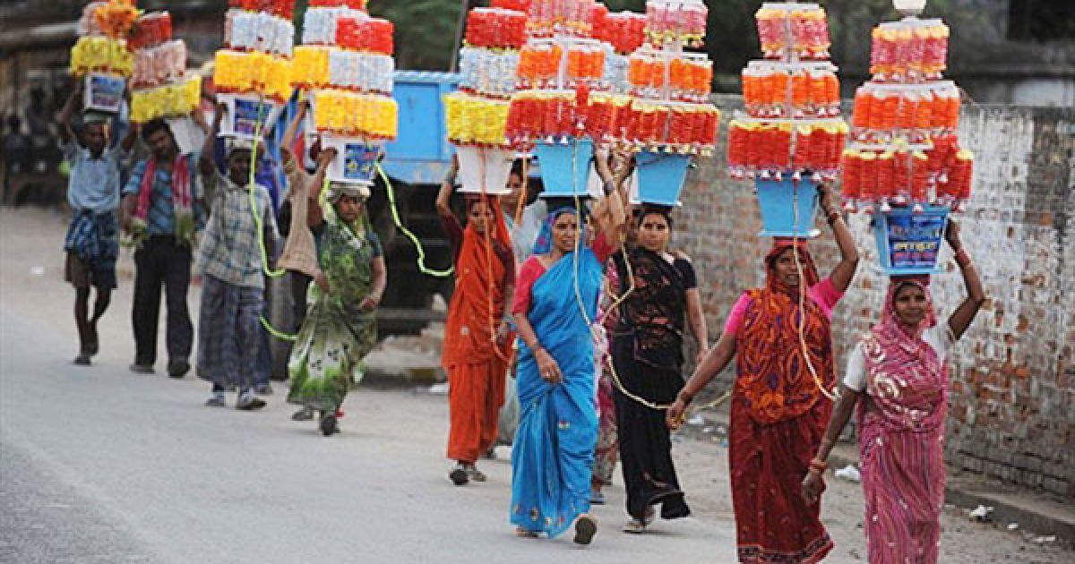 Індія, Аллахабад. Індійські жінки несуть декоративні лампи, які традиційно використовують під час весільної ходи. Заробіток цих найманих працівників у Аллахабаді становить менше 2 доларів на день. @ AFP