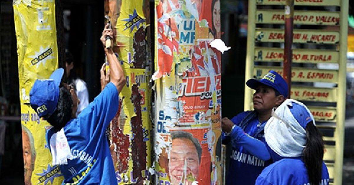 """Філіппіни, Маніла. Двірники прибирають плакати, що залишились після виборчої кампанії. Беніньо Акіно має найбільші шанси стати наступним президентом Філіппін. Він отримав народну підтримку, якої не бачили у країні з часів руху """"Народна сила"""", очолюваного його батьками. @ AFP"""