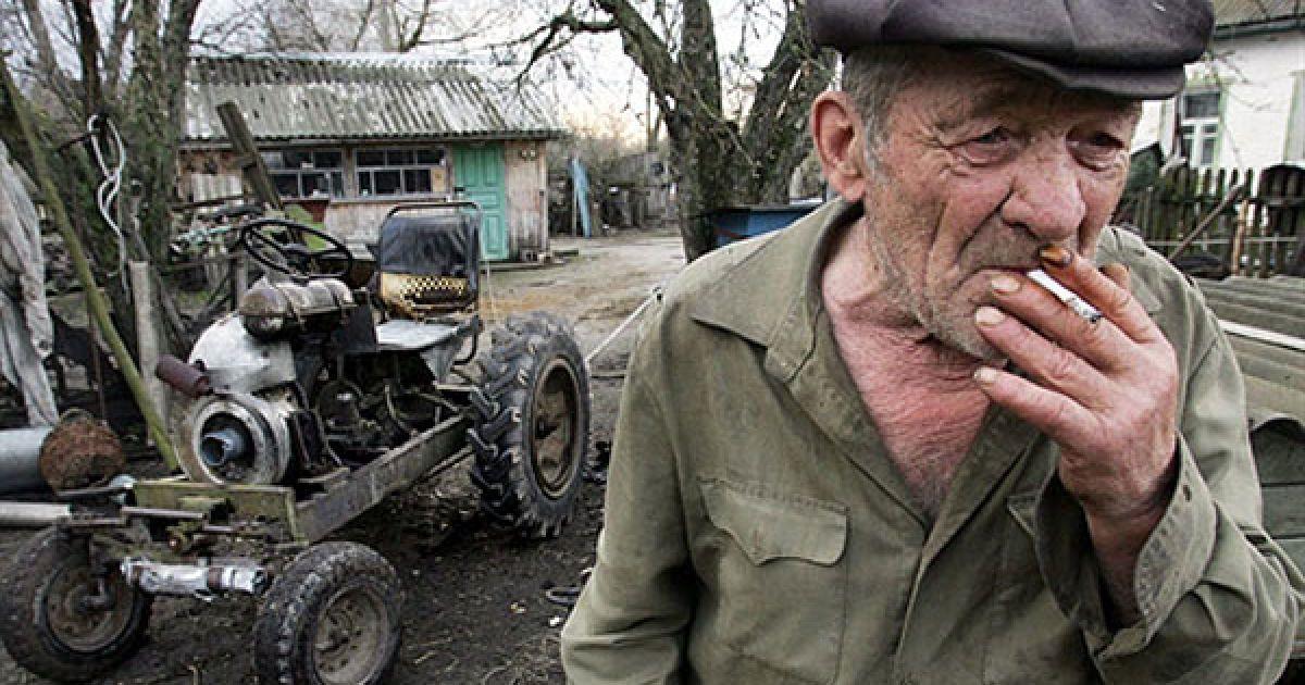 Україна, село Ільїнці, 30-км зона. Мешканець Ільїнців Микола Коваленко поруч з трактором, який він зібрав власноруч. @ AFP