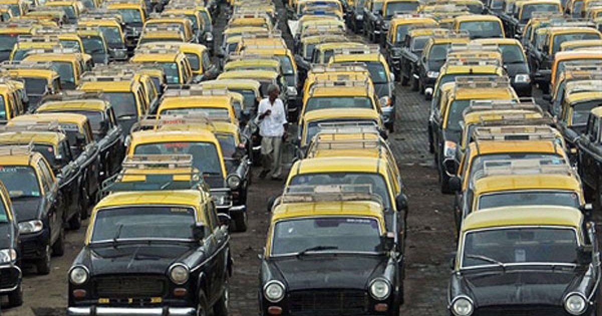 Індія, Мумбаї. Таксист ходить між припаркованих таксі у аеропорту міста Мумбаї. Майже 85 тисяч водіїв таксі та 100 тисяч авто-рікш оголосили страйк на знак протесту проти підвищення цін на природний газ. @ AFP