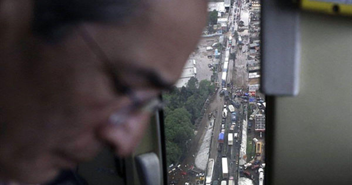 Президент Гватемали Альваро Колом летить над містом Палін, яке постраждало від стихії. @ AFP