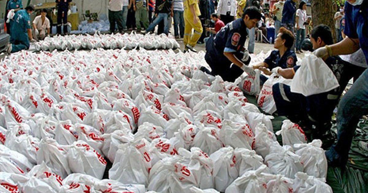 Таїланд, Бангкок. Члени Фонду порятунку несуть сумки з трупами до моргу в буддійському храмі у Бангкоку. В храмі тайська поліція знайшла людські залишки, приховані працівниками нелегальних клінік абортів у Бангкоку. Представники поліції знайшли більше 1000 трупів і заявили, що очікують подальші жахливі знахідки. @ AFP